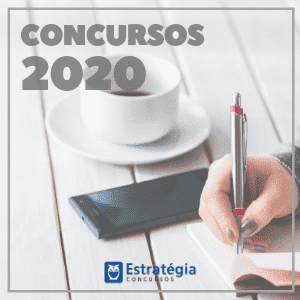 concursos 2019 - a imagem ilustra uma mão de uma pessoa, escrevendo com caneta, ao lado, uma xícara de café e um celular