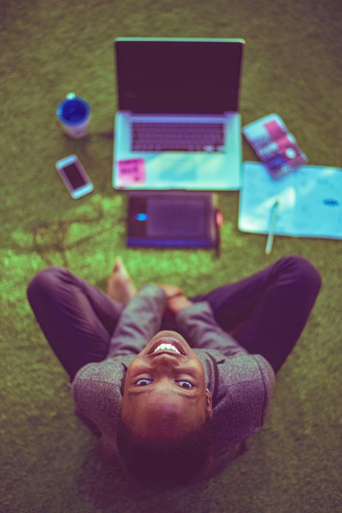 Pare de se preocupar com o que não está no seu controle e colha os benefícios. Homem estudando na grama e feliz.