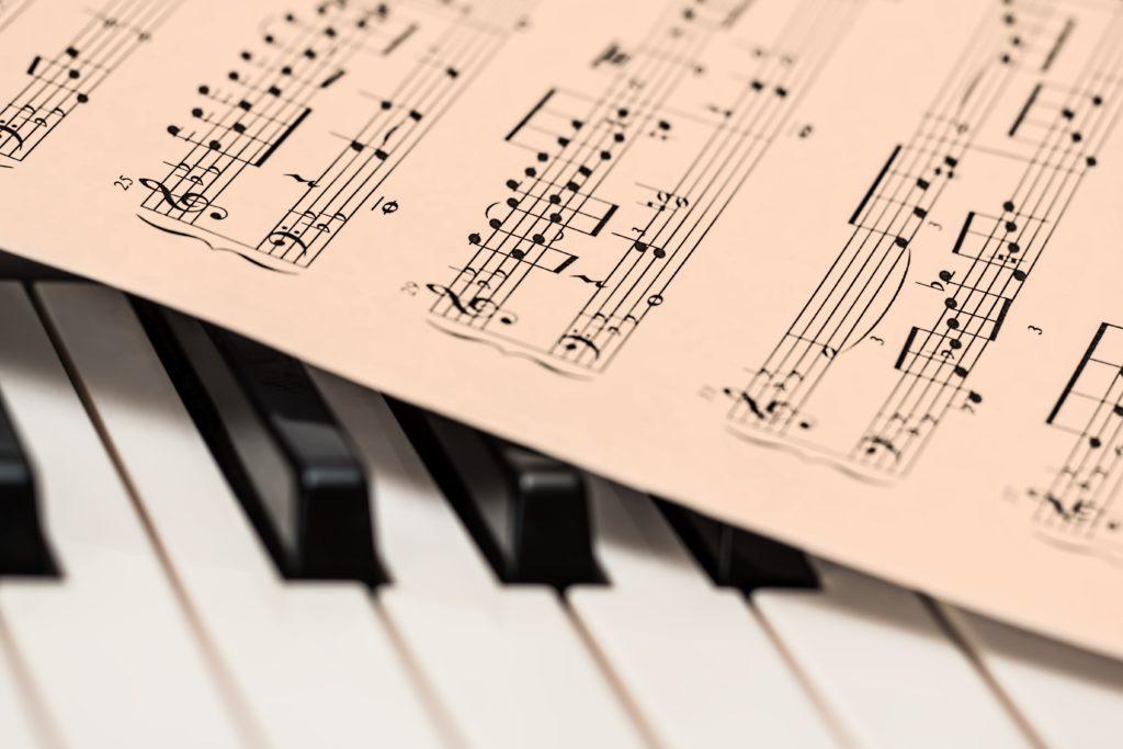 Imagem parcial de um piano e de uma partitura de música