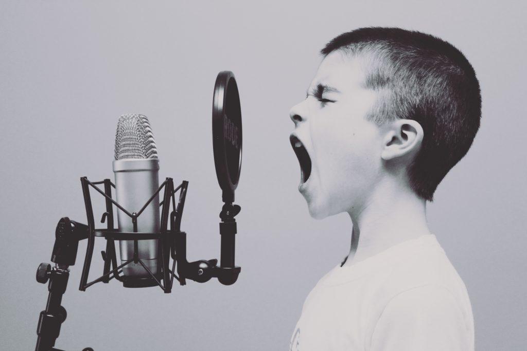 Foto de um menino cantando uma música
